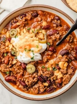 Slow cooker chili in a bowl with toppings.