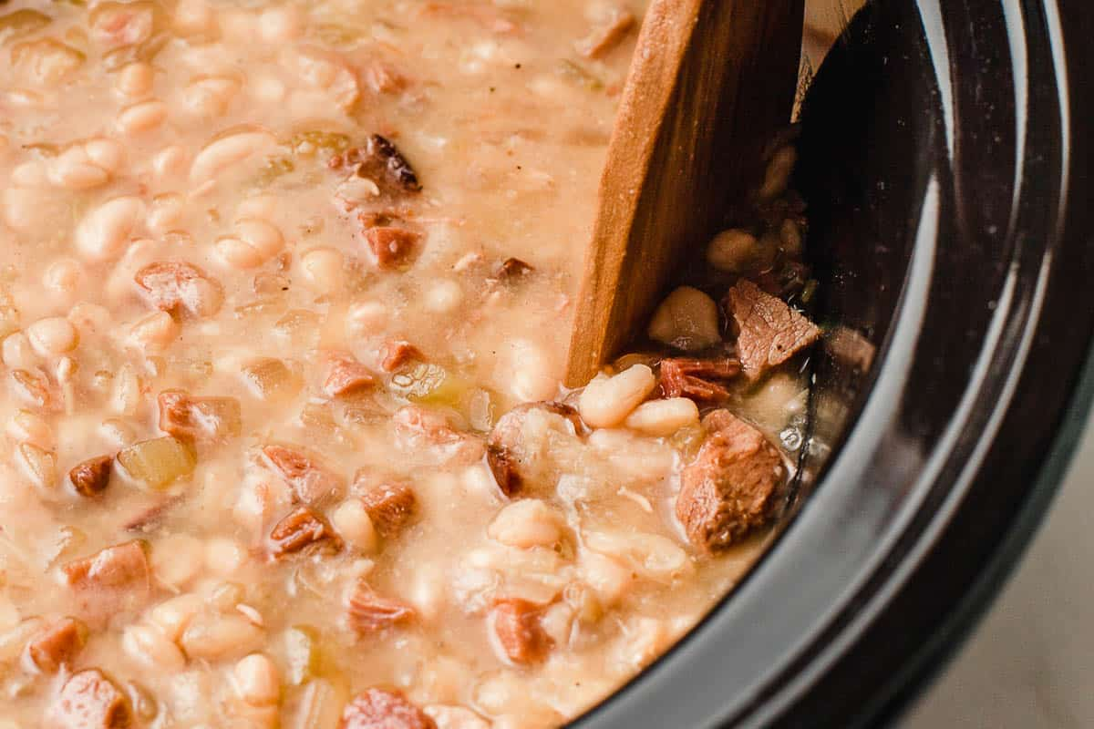 Smashing white beans on the side of the slow cooker.