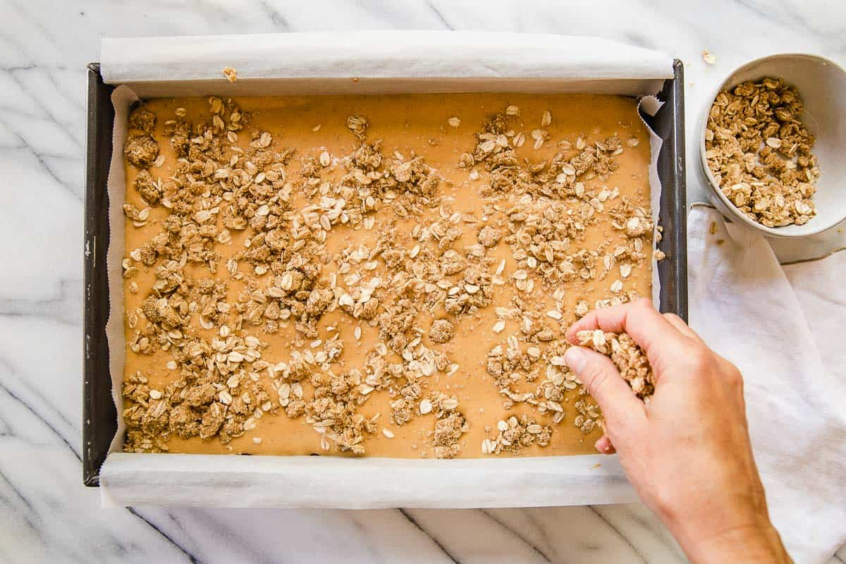 Sprinkling final layer of crumb topping onto pumpkin bars.
